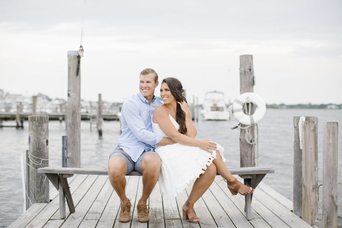 engaged couple sitting together on dock in sea bright
