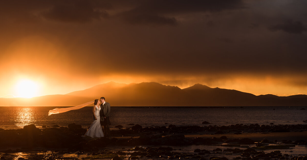 Bride and groom with veil flying at Seamill Hydro at sunset, by Andi Watson wedding photographers.