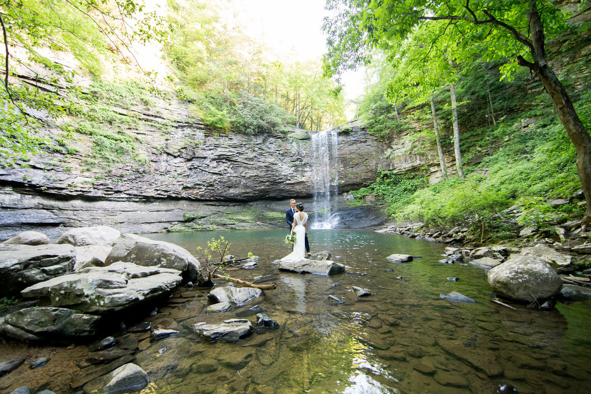 Waterfall backdrop for wedding vows.  Photo by destination elopement photographer Rebecca Cerasani