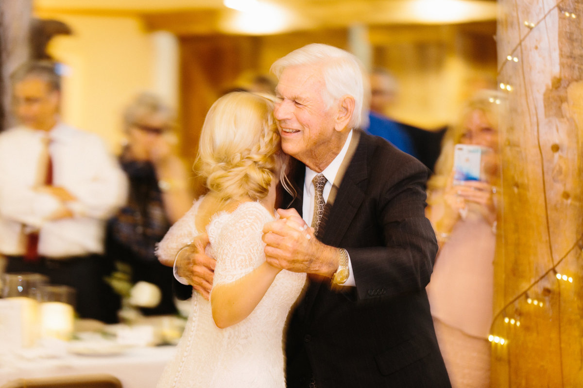 A woman in a wedding dress dances with her grandfather.