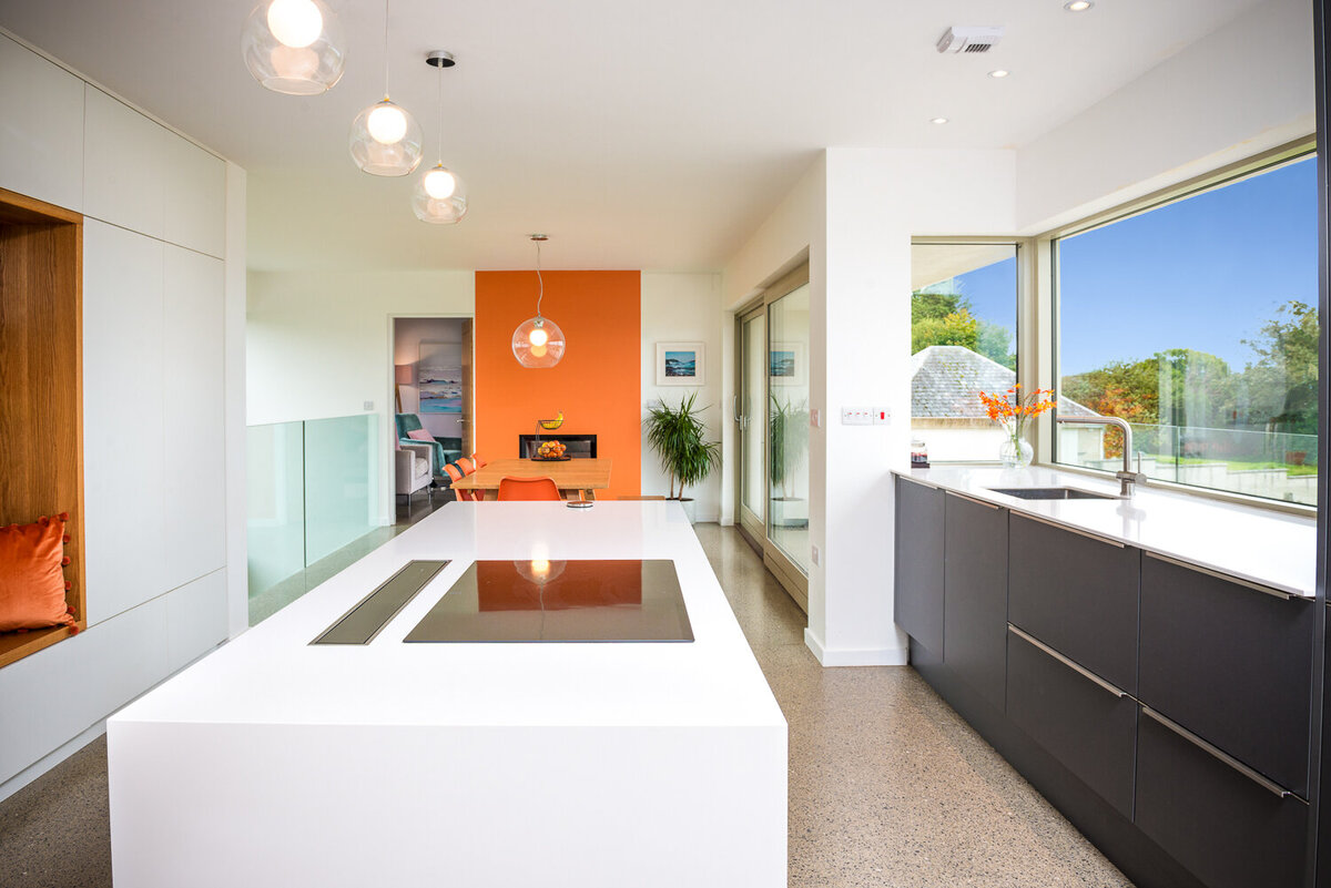 Modern kitchen with orange feature wall, island with cooker and grey kitchen units