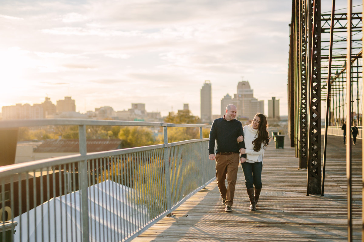Man walking with women on Hays Street Bridge while on their engagement session with Expose The Heart Photography.