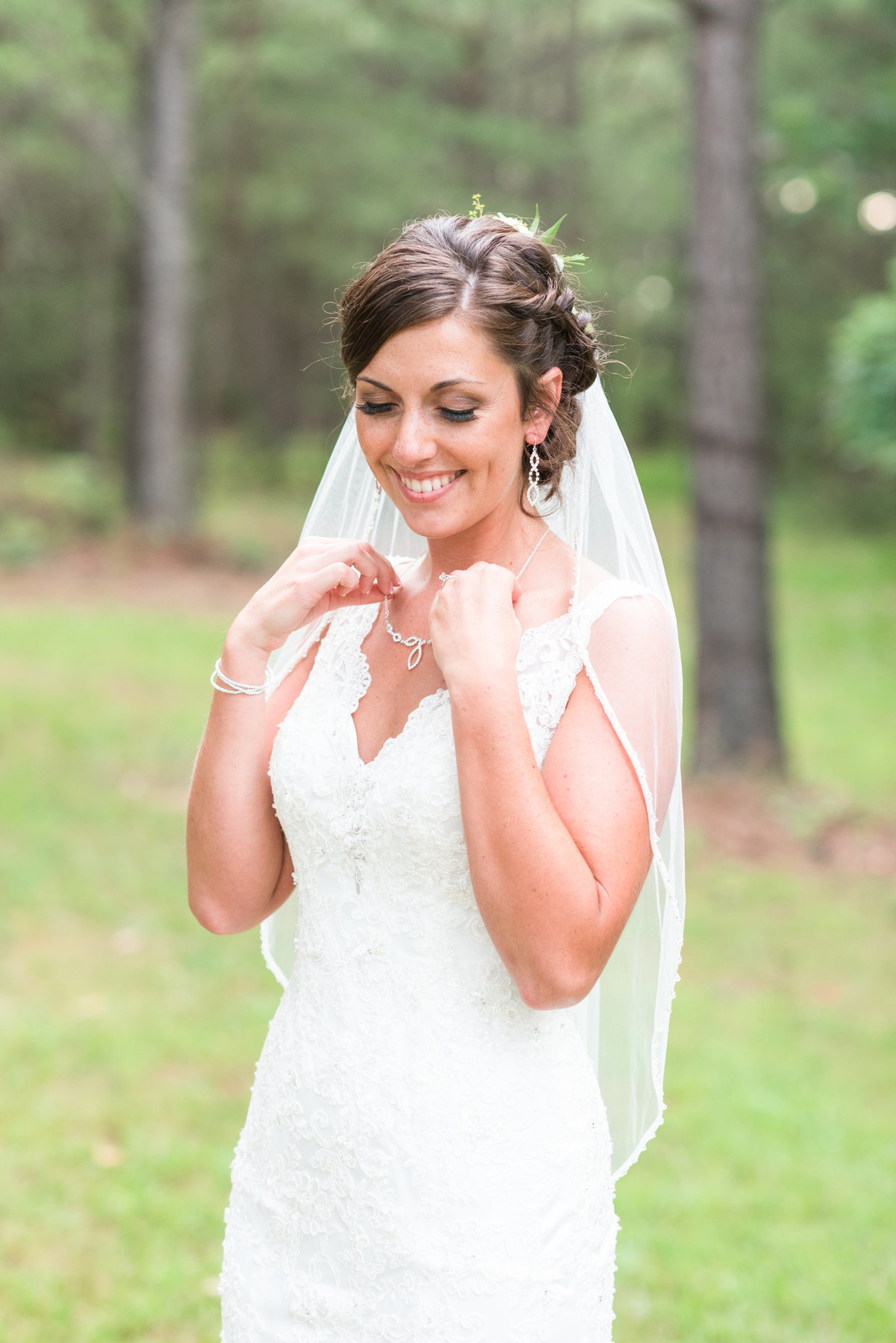 a bride wearing a laced thin strapped wedding dress fixing her necklace while looking off at Meadows at Walnut Cove