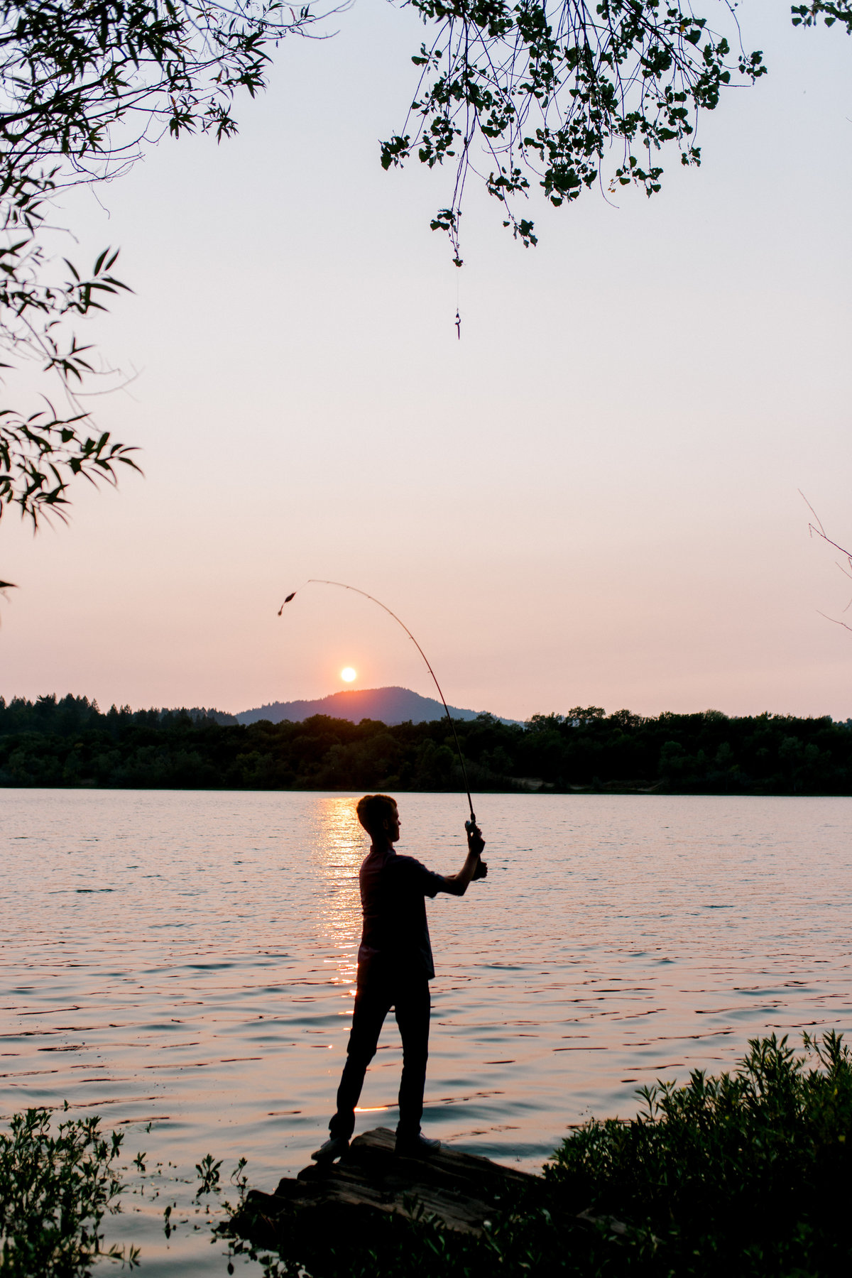 senior guy fishing in lake at sunset