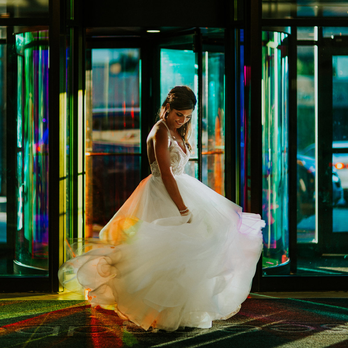 The bride spins as the colorful lights shine through the windows and her Miss Hayley Paige wedding gown.