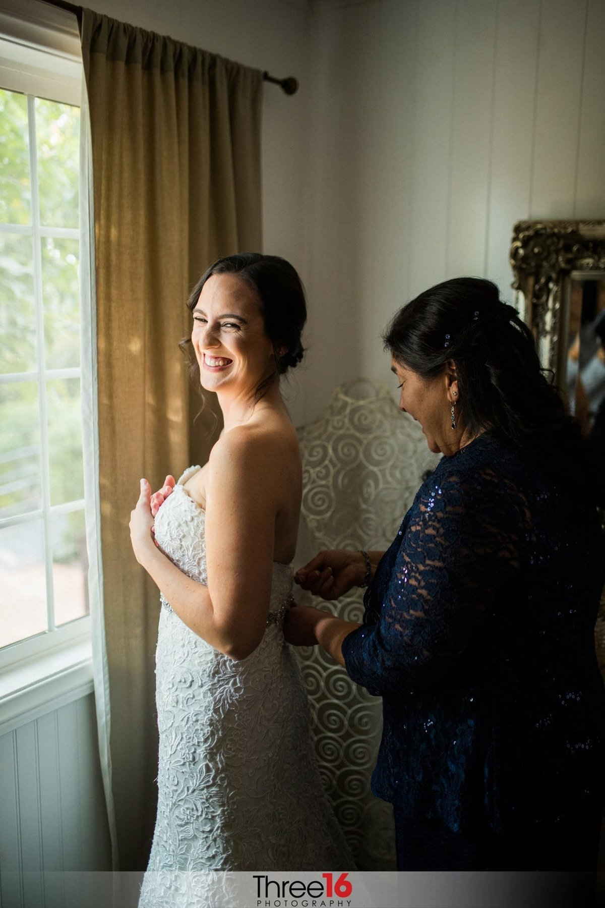 Bride having her dressed zipped up
