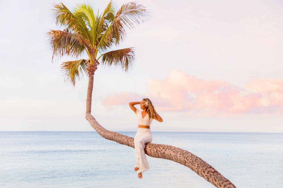Maui bride poses on a palm tree in Hawaii