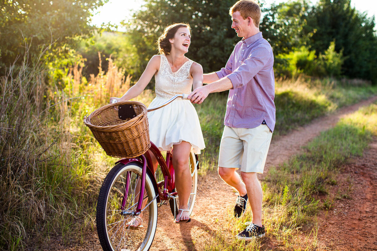 joyful candid engagement photo of couple on bike