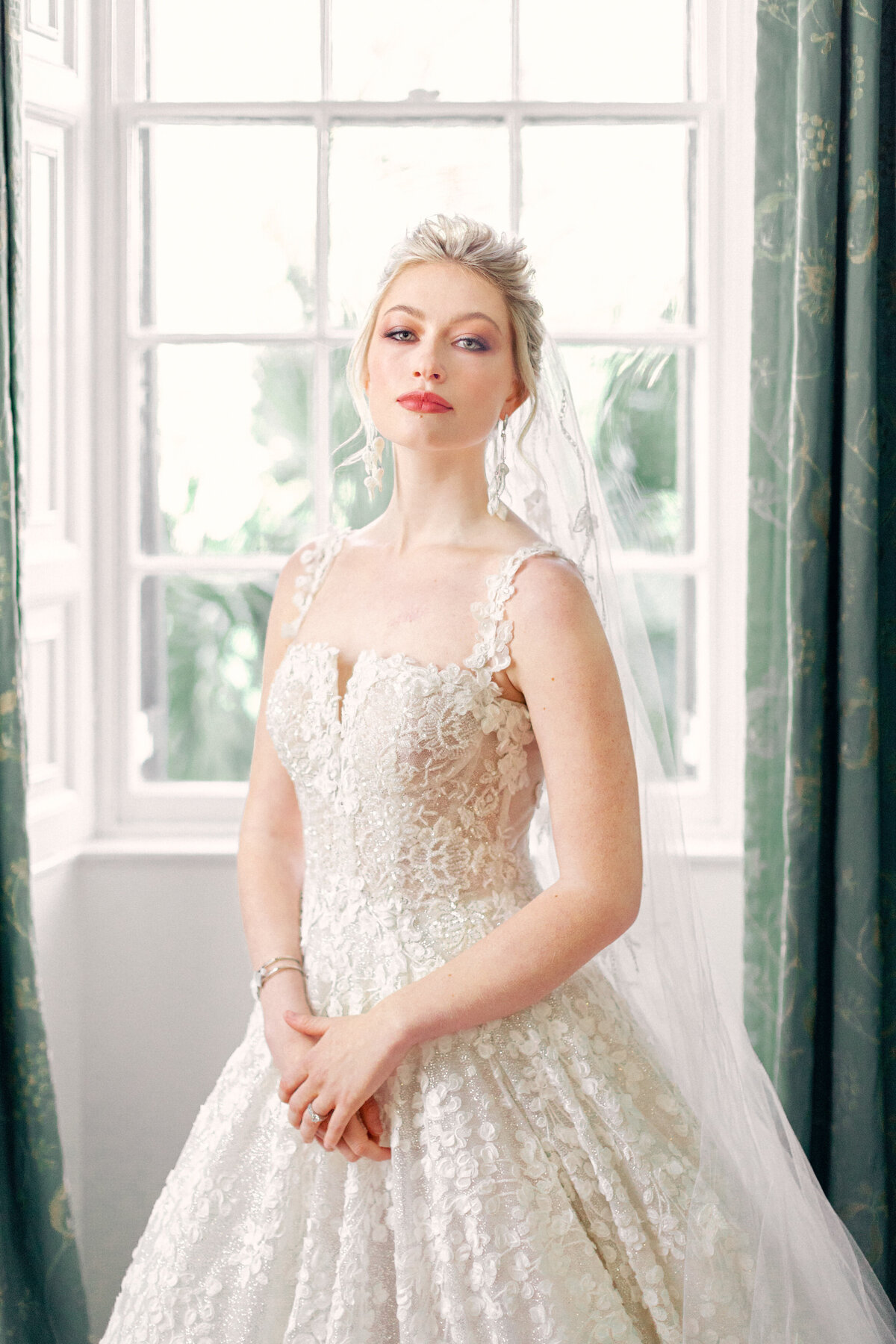 Bride in white lace wedding dress standing at window with green curtains at Lowndes Grove Charleston