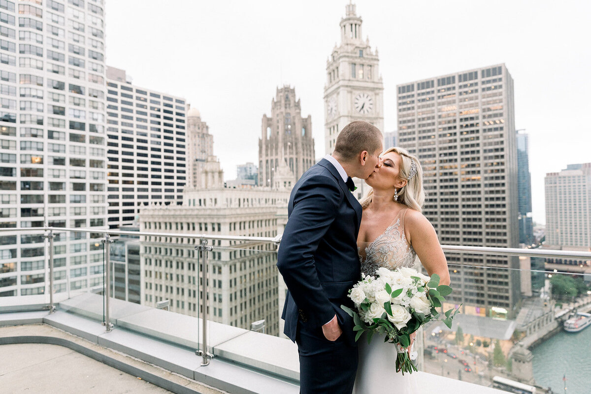 bride and groom kissing on terrace in downtown chicago
