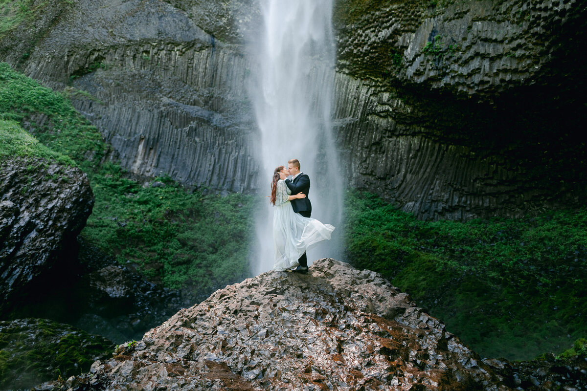 girl in dress kissing man in suit on top of a rock in front of waterfall in Oregon