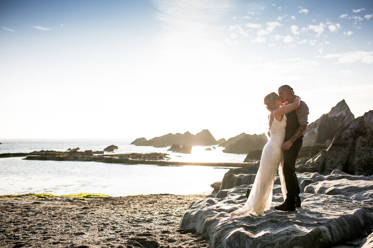 Bride and Groom kissing on the beach at Tunnels Beaches Devon
