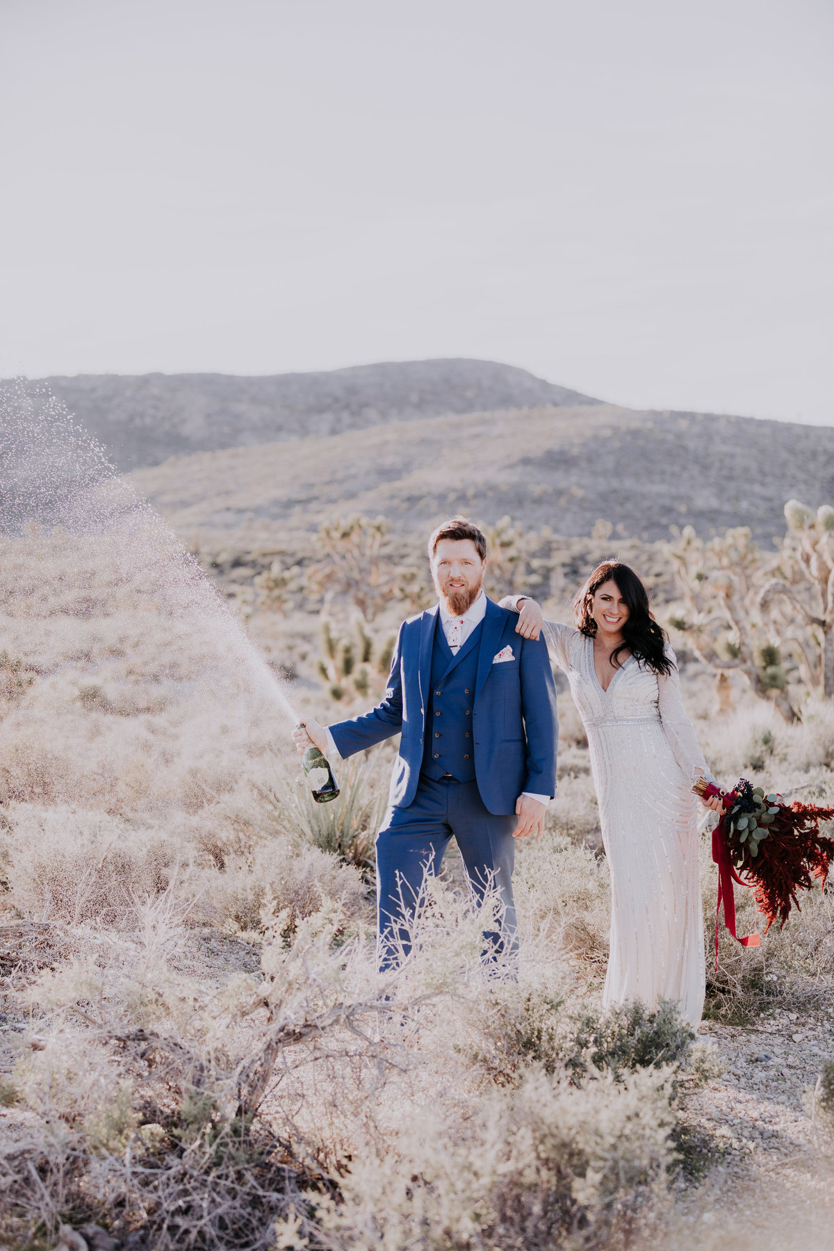 Lake Tahoe elopement photographers couple sprays champagne in desert