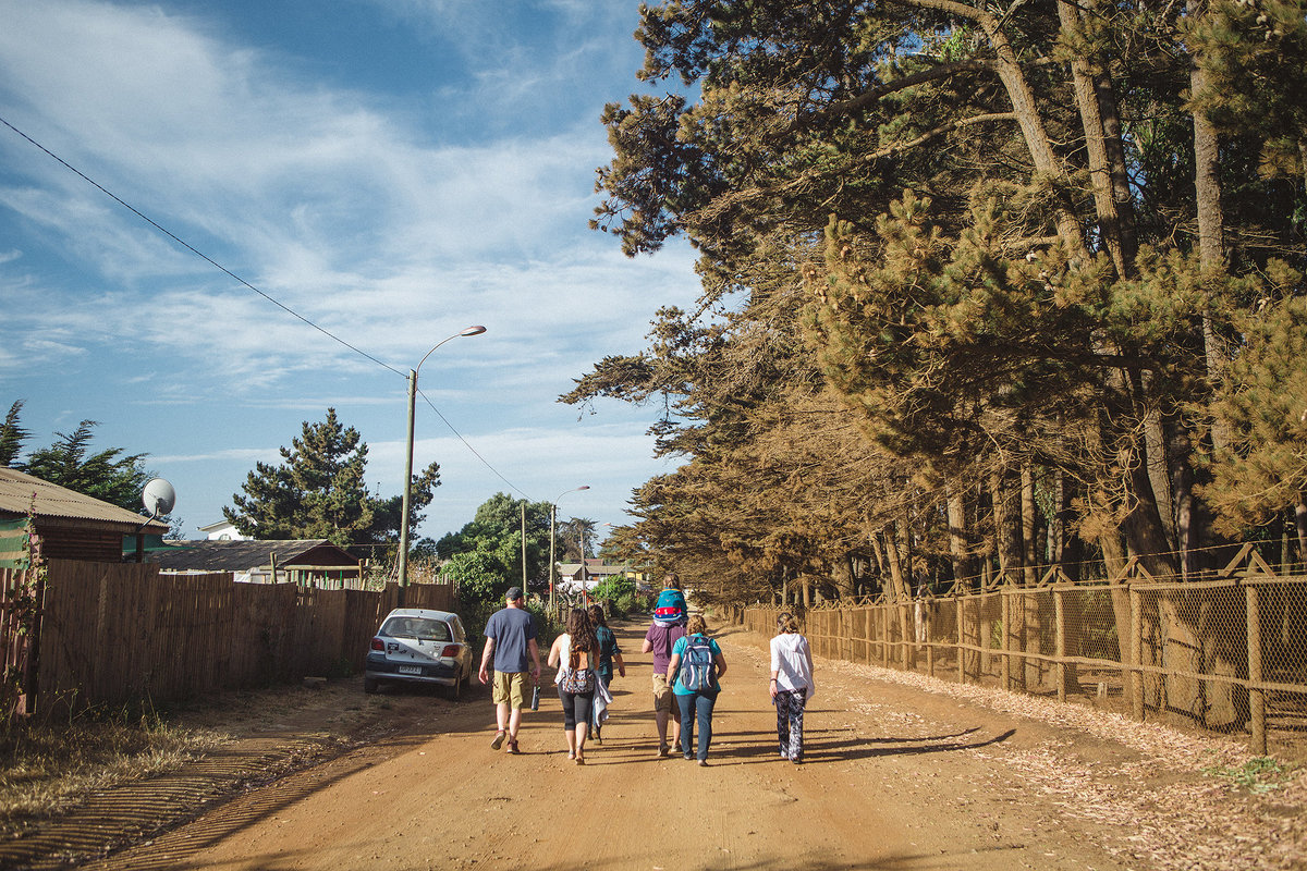 group of people walking along dirt raod in pichilemu chile