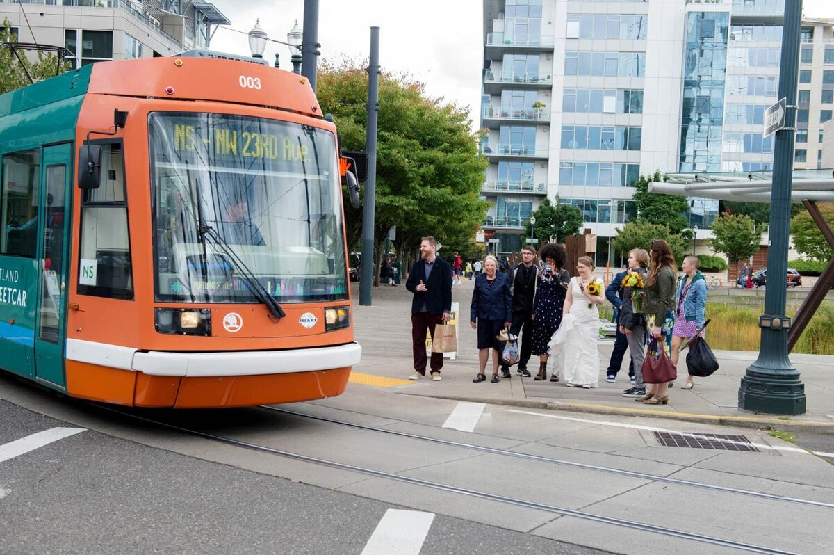 a bride and her wedding guests stop and wait for the portland streetcar to pass