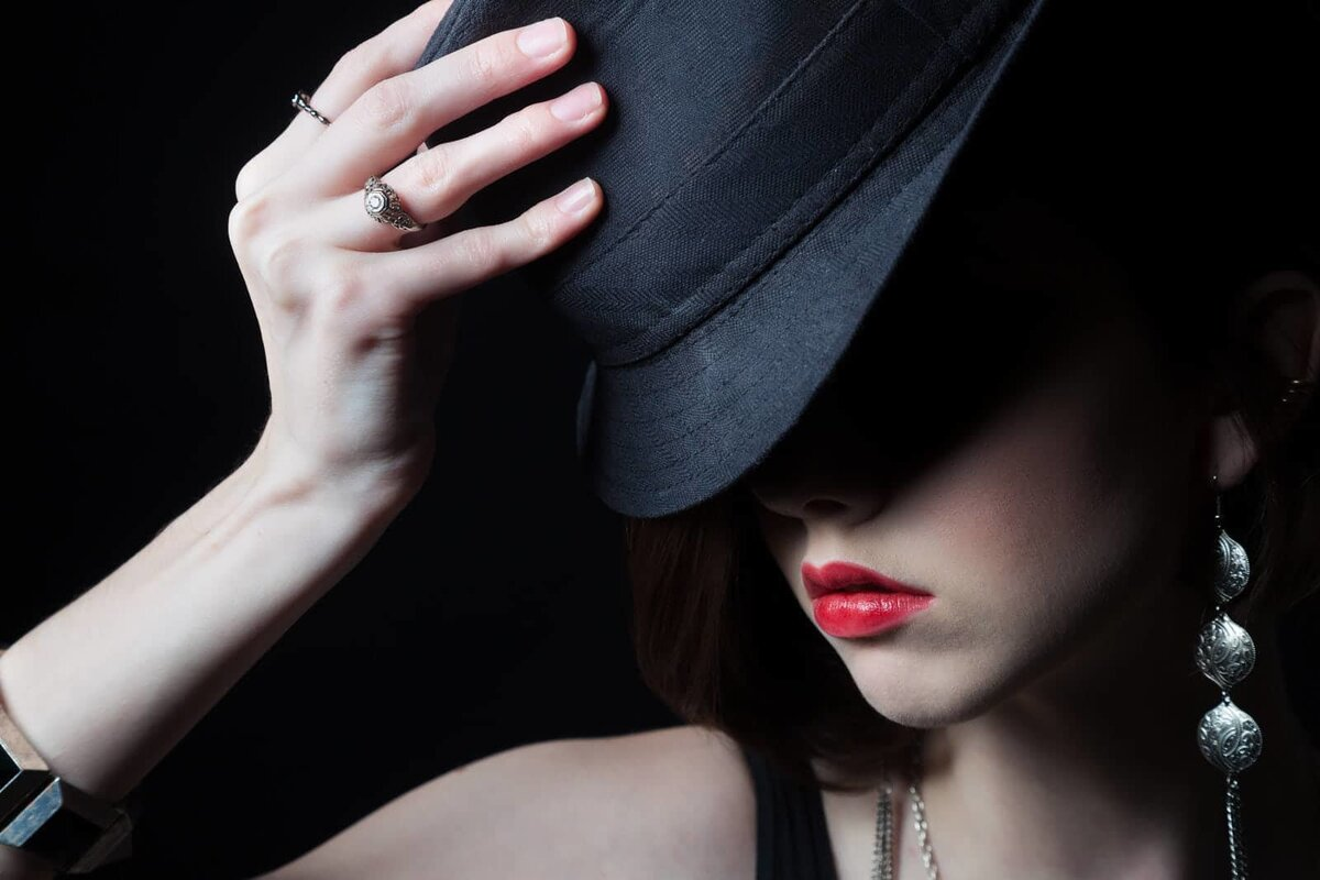 dramatic portrait of Atlanta red lipstick girl holding fedora over eyes