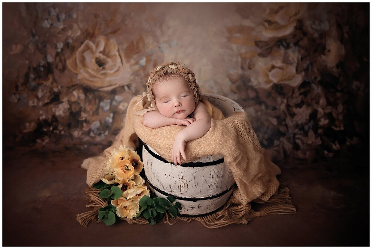 Baby girl in a bucket with yellow flowers