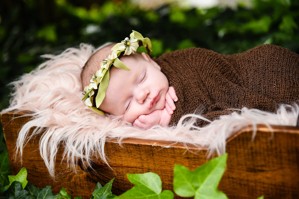 Beautiful Mississippi Newborn Photography: newborn girl with floral crown lays in a bed of ivy