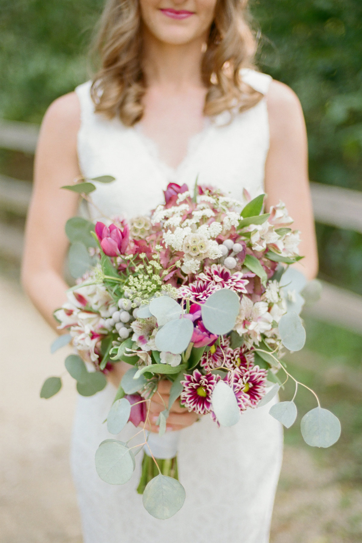 bride holding lush purple and green bouquet