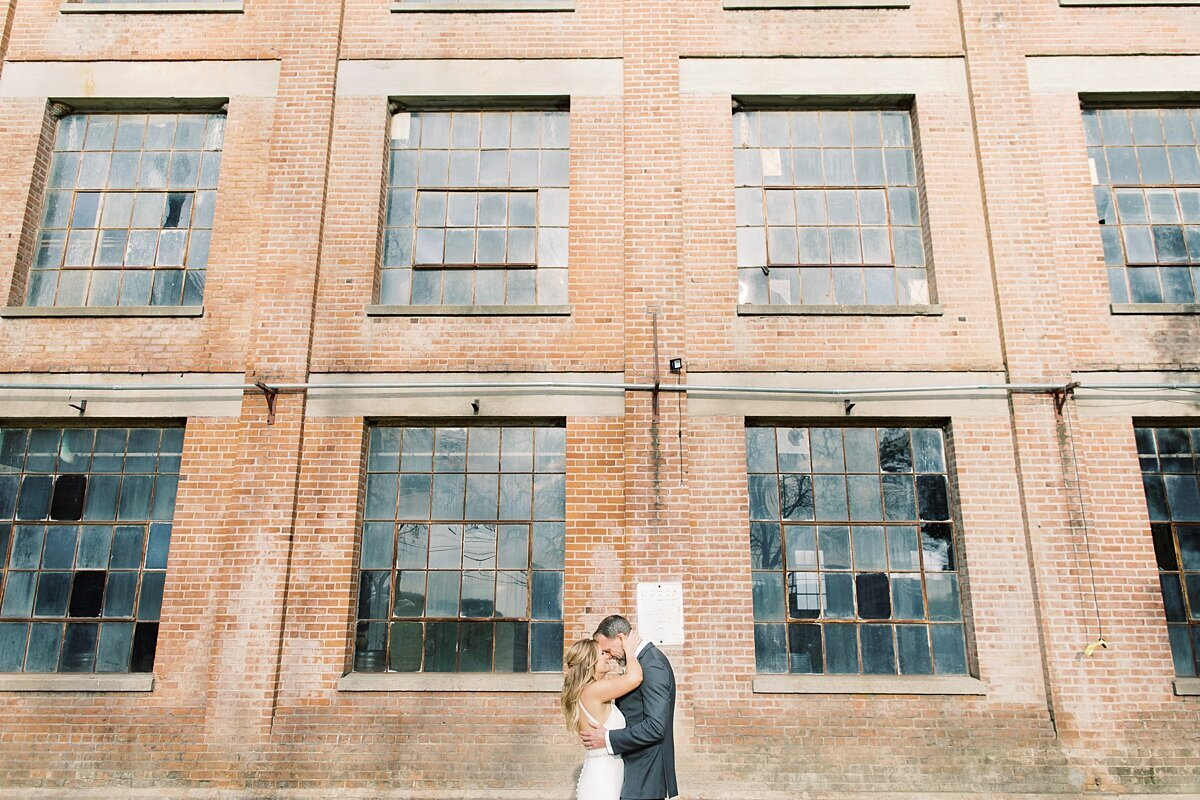Bride and groom kiss in celebration of their industrial wedding