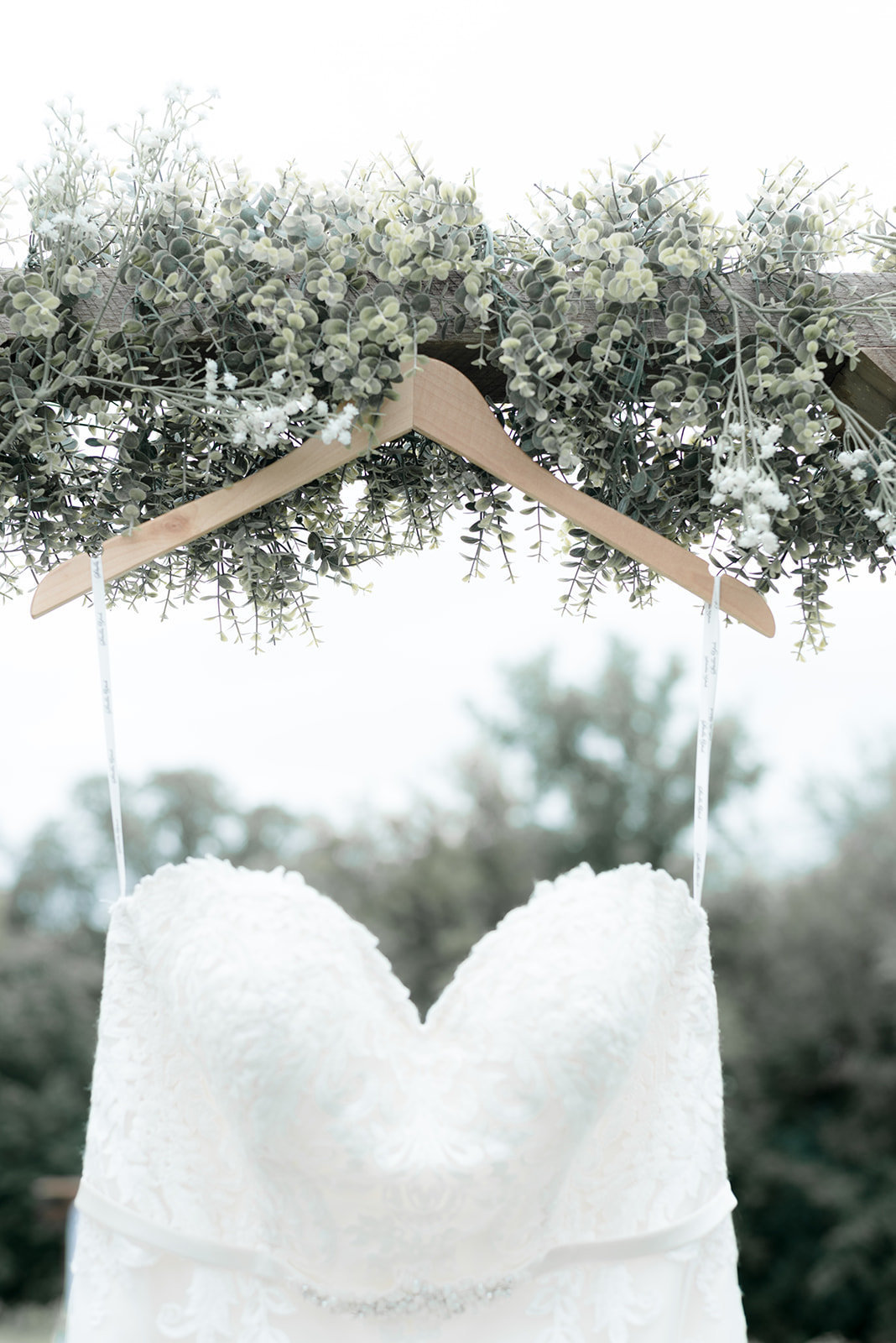 Lace strapless wedding gown hanging from seeded eucalyptus on a white barn door in Prescott Wisconsin
