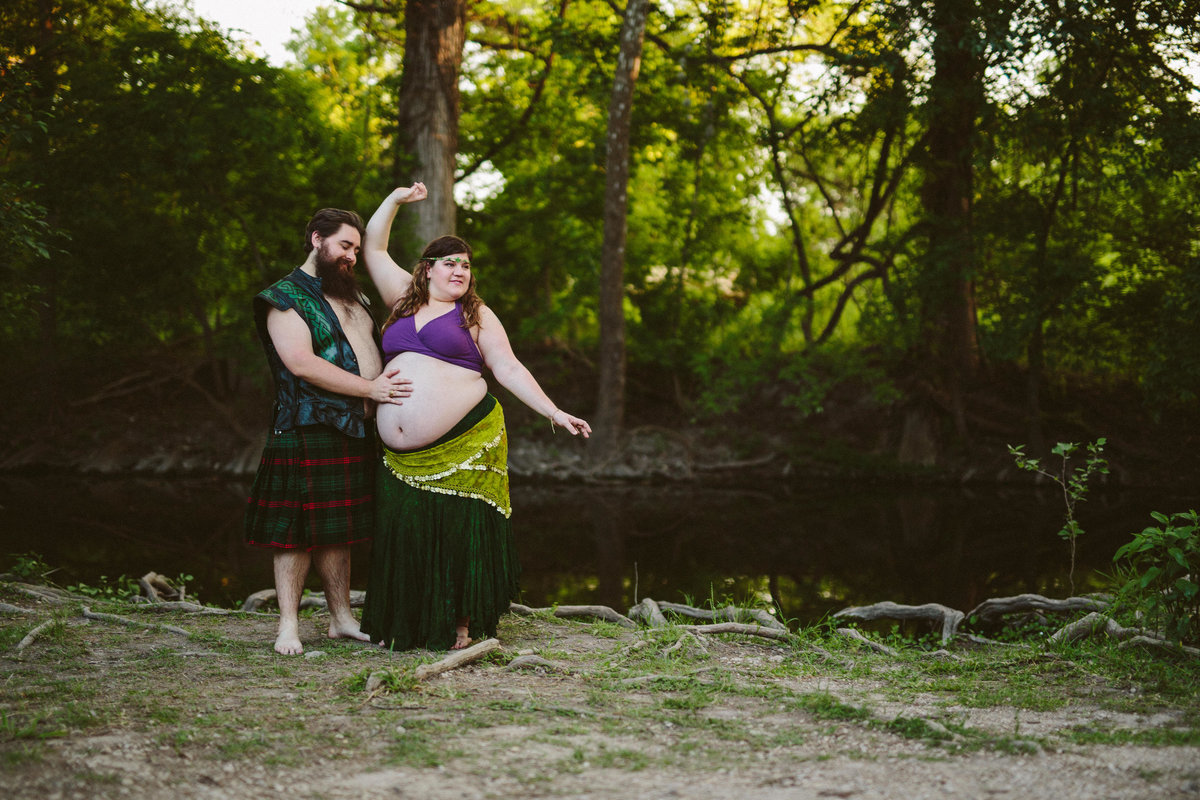 Pregnant mother and father dancing next to river in Cibolo nature Center