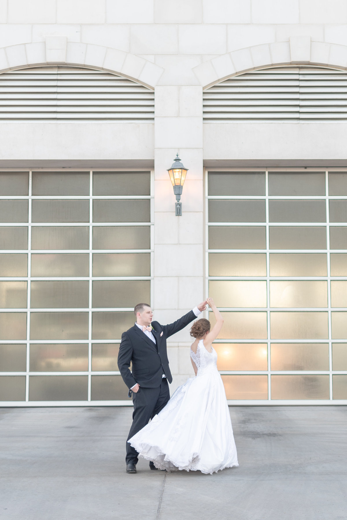 groom spinning bride in front of fire station