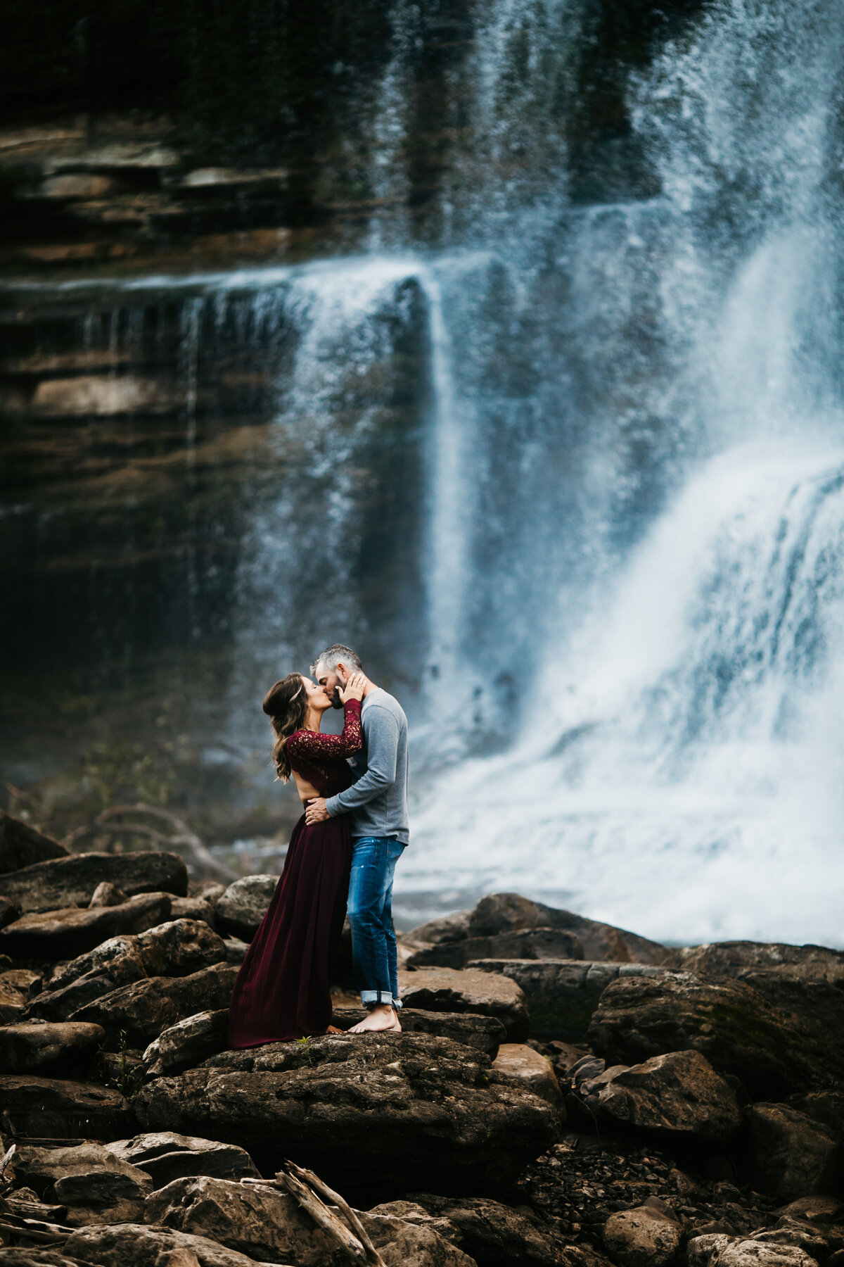 couple kissing next to a waterfall