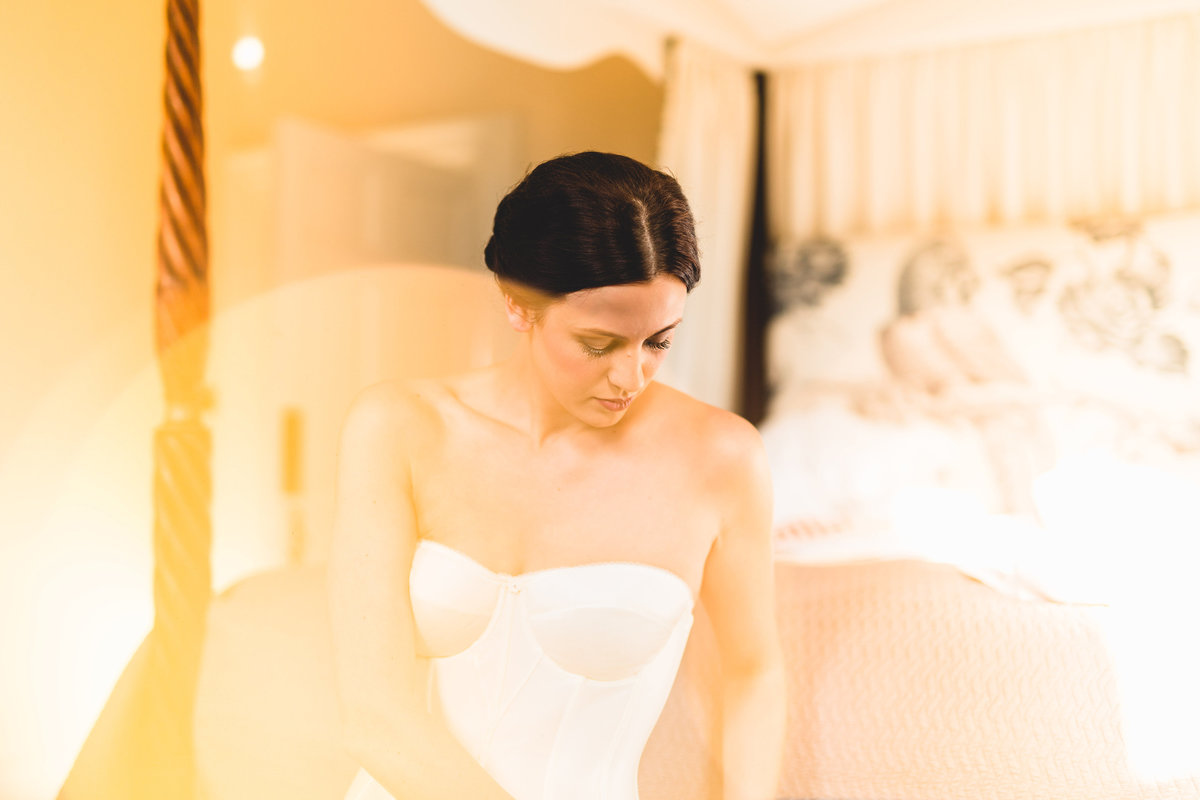 bridal boudoir photograph of bride sat on bed in underwear tasteful