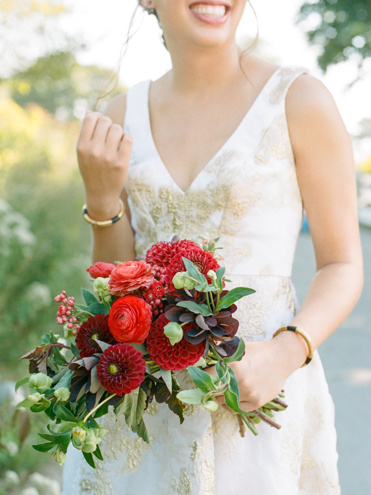 bride holding colorful red garden bouquet