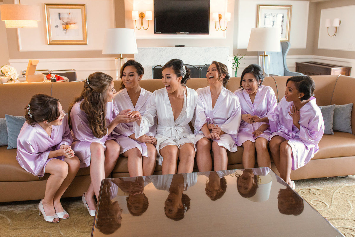 photo of bride with bridesmaids laughing inside bridal suite at The Garden City Hotel