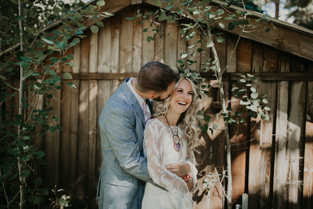 Groom kisses brides cheek while she smiles and laughs on their wedding day at Mountain Spring Lodge in Washington