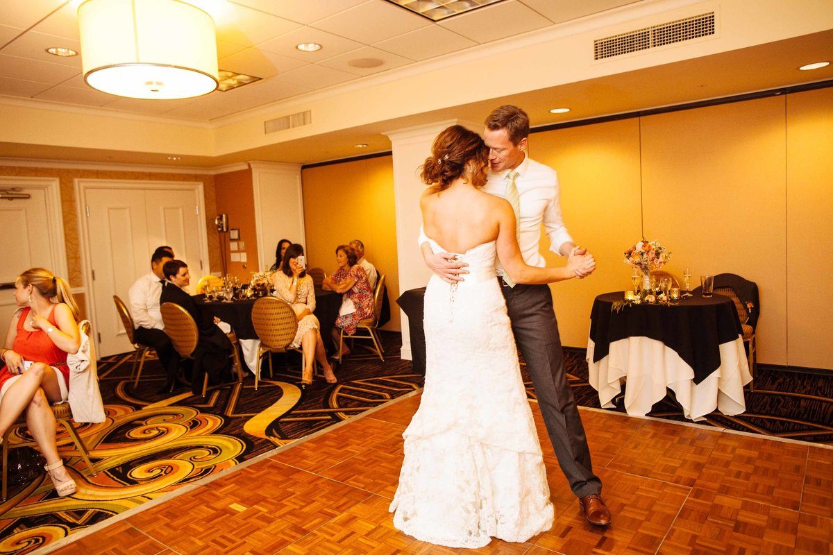 A bride and groom dance together while their friends watch.