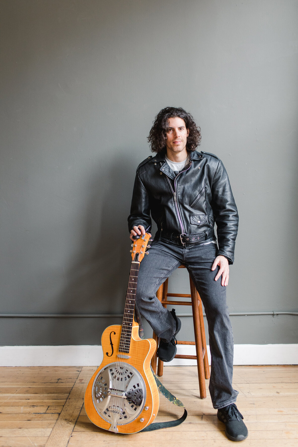 a curly haired man sitting on a stool and a guitar in one hand resting  in front of him