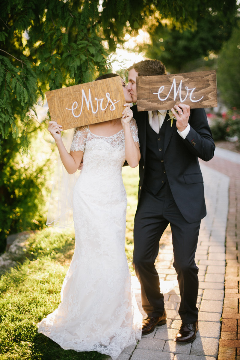 fun playful wedding mr. mrs. signs kiss candid funny bride and groom candid wedding photography
