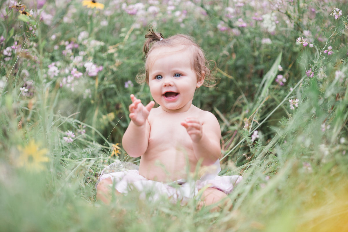 Jacksonville family photographer captured an image of a smiling little girl sitting in a field of wild flowers