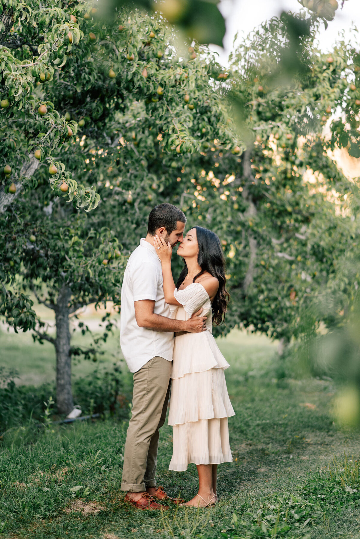 Couple kissing in an orchard at Beecher Hill House during engagement session