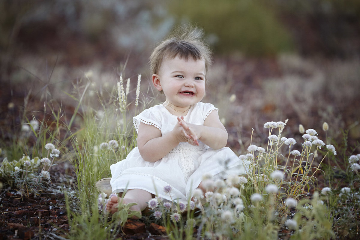 Baby girl sitting in a field with flowers clapping her hands and smiling