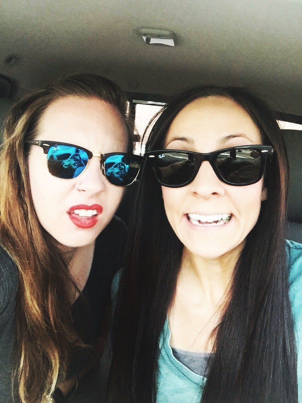 Two girls pose for a selfie in a car