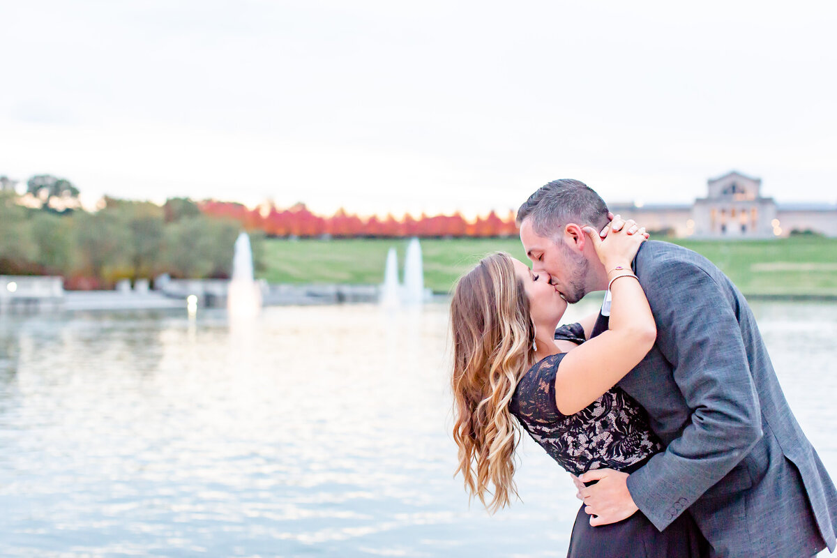 Fall Sunset Engagement  Session with black dress couple kissing  by water at The Grand Basin  in Forest Park in St. Louis by Amy Britton Photography Photographer in St. Louis