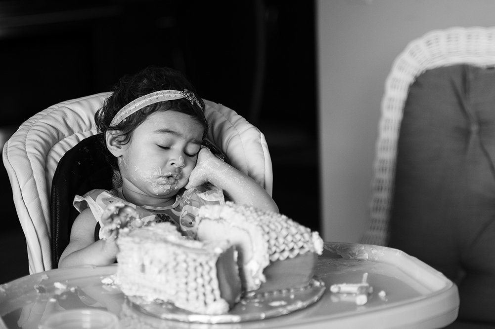 black and white photo of overwhelmed baby at cake smash
