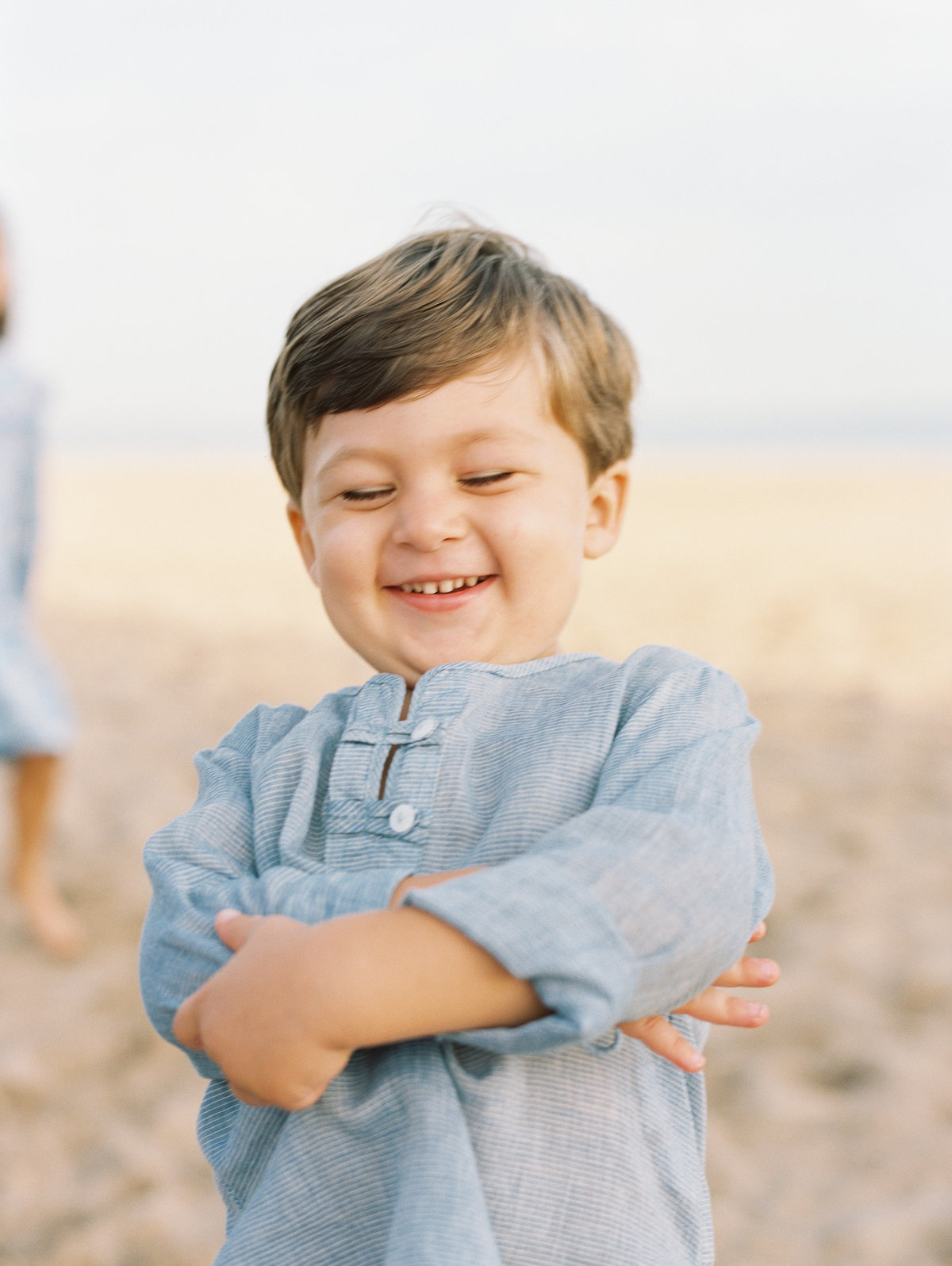 little boy laughing at beach