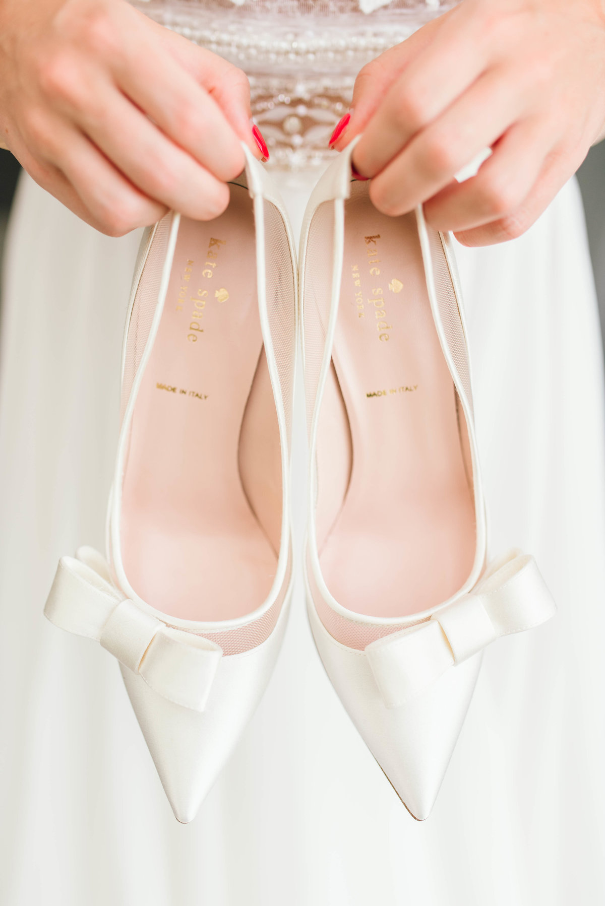 Bride holding Kate Spade wedding shoes