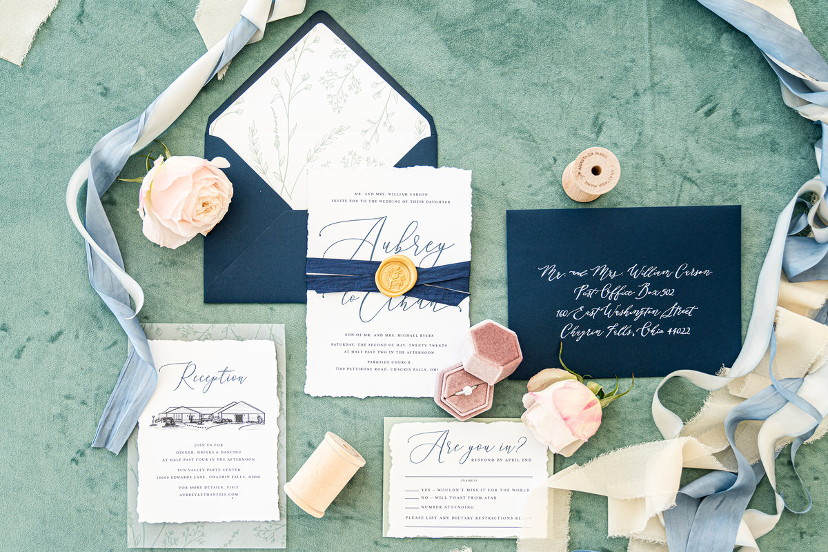 Beautiful deckled edge wedding invitation with modern calligraphy. Wrapped with a navy silk ribbon and sealed with a gold wax seal.