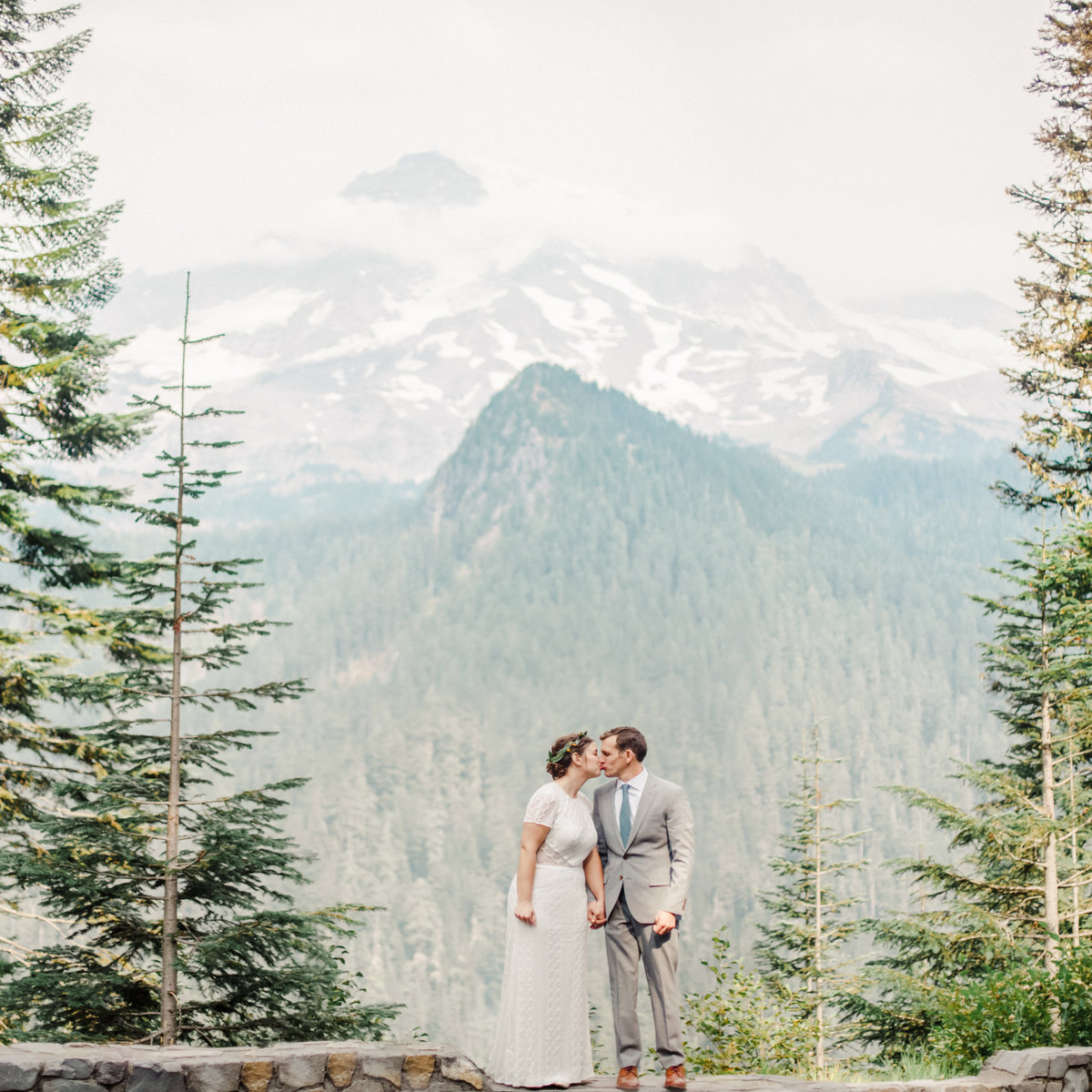 bride and groom stand on ledge of national park with mt rainier in background