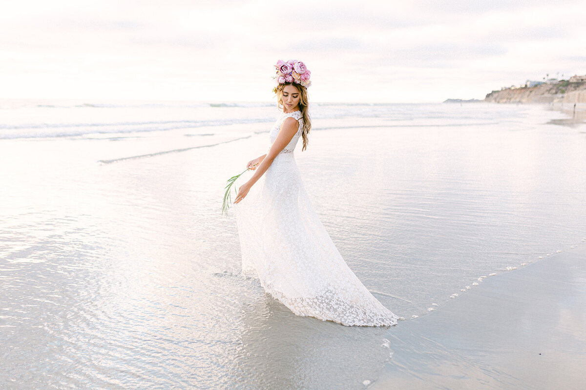 bride in wedding dress walking into the ocean