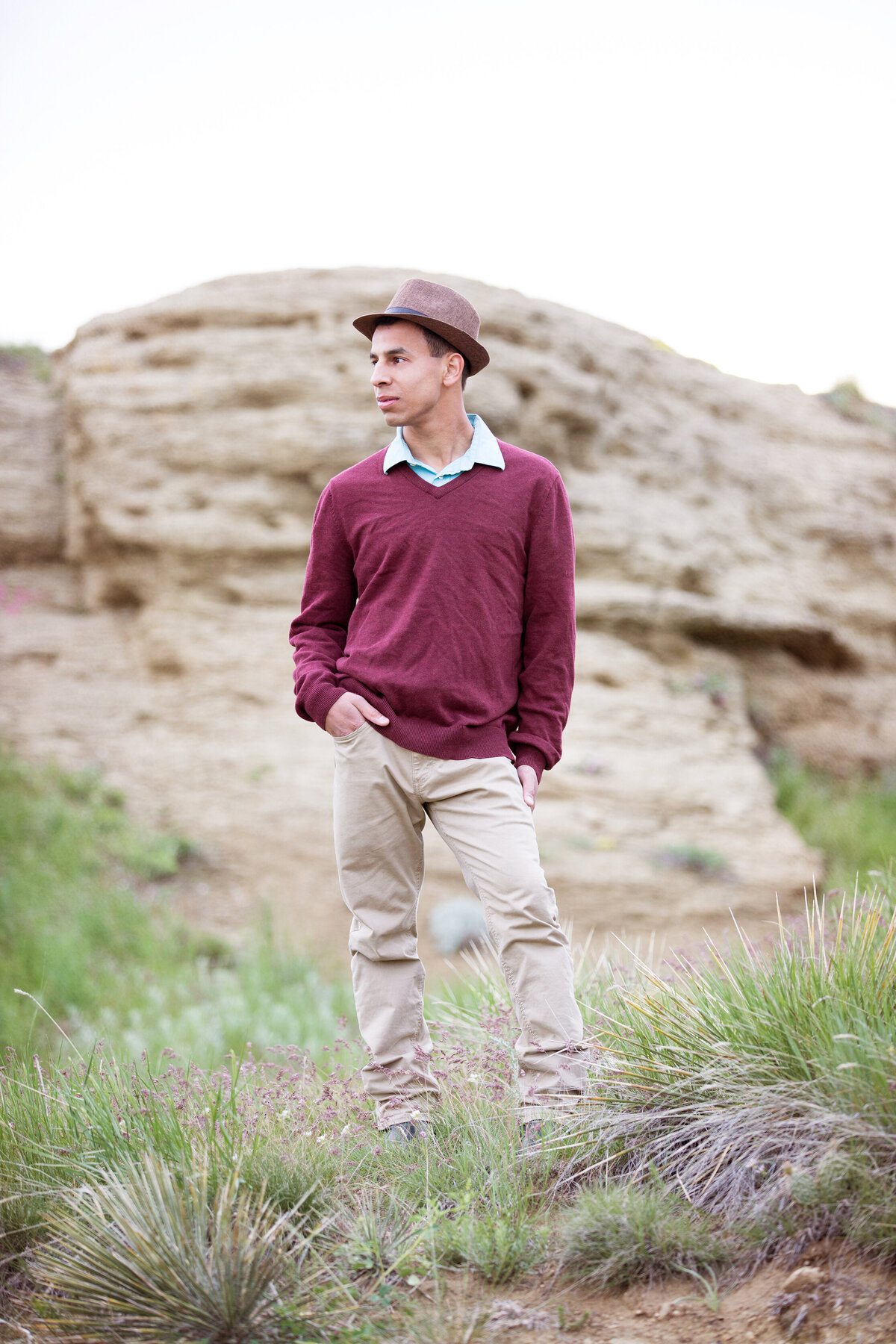 pictures of high school senior wearing maroon shirt, kakis and hat. Photographed at Swords Park with yucca plants near the airport in billings mt.