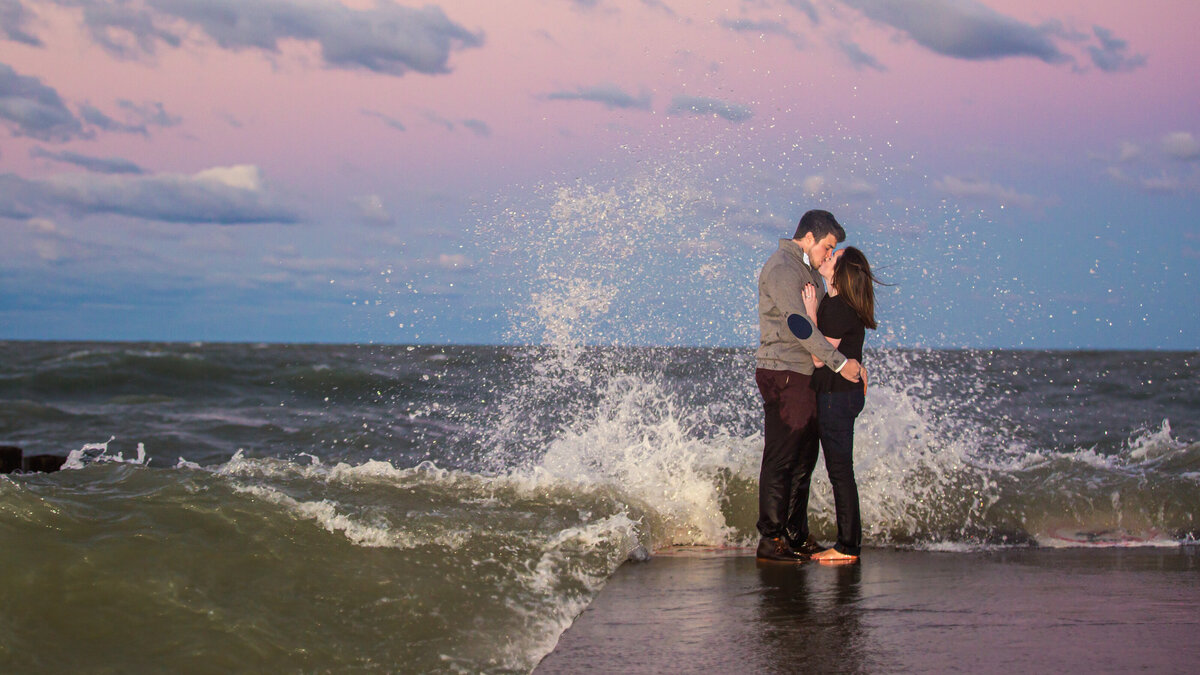 Waves crash over a couple taking sunset engagement photos in Chicago.