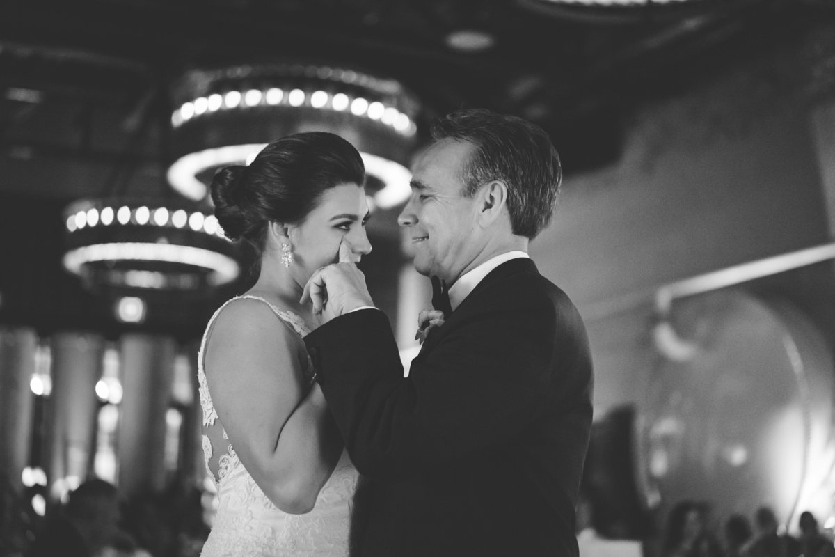 father wipes tear during father daughter dance at wedding receptions at Hotel Emma wedding venue at The historic Pearl