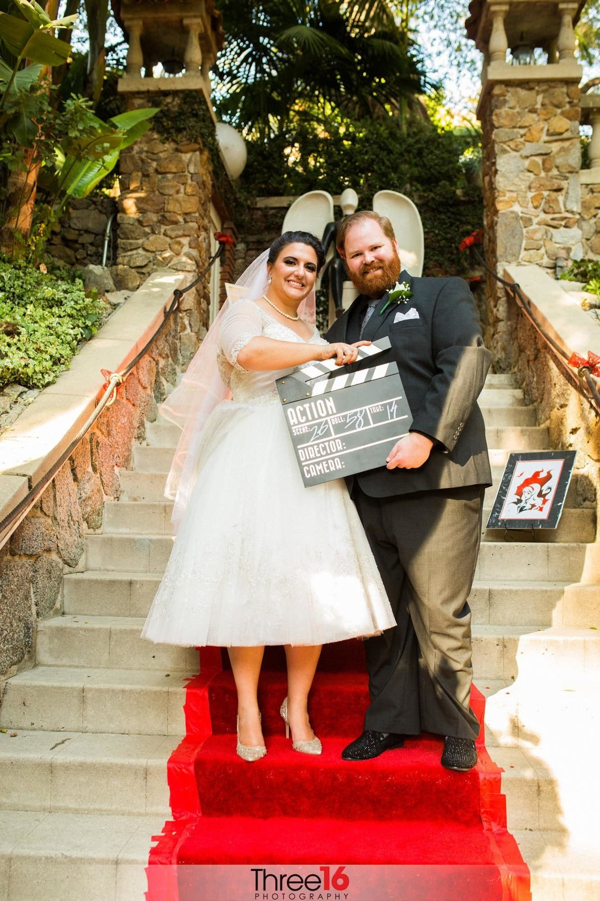 Bride and Groom pose on the red carpeted staircase